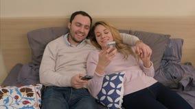 Belle coppie che si siedono sul letto e che guardano foto dal viaggio sullo smartphone, schermo commovente, sorridente Fotografia Stock