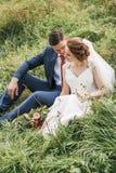 Belle coppie che si siedono sul prato verde in alta erba Fotografia Stock Libera da Diritti