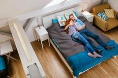 Belle coppie che si trovano sul letto e sul riposo Fotografia Stock
