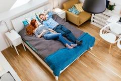 Belle coppie che si trovano sul letto e sul riposo Immagini Stock