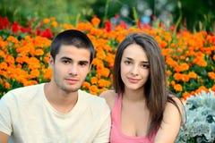 Belle coppie che sorridono accanto ad un fondo del fiore Fotografie Stock