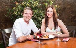 Belle coppie che sorridono avendo deserto fuori sul terrazzo Fotografia Stock Libera da Diritti