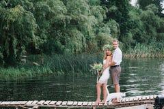 Belle coppie con un mazzo sul ponte con un gatto bianco Fotografie Stock