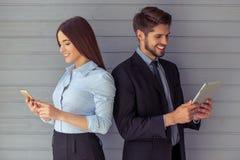 Belle coppie di affari con l'aggeggio Fotografia Stock Libera da Diritti