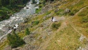 Belle coppie di nozze dello sposo e della sposa su una roccia stock footage