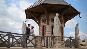 Belle coppie di nozze esaminarse vicino al castello magnifico di pietra con le statue stock footage