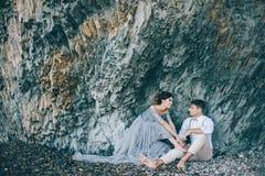Belle coppie felici dal mare vicino alle rocce, sedendosi a piedi nudi, sorridendo, parlando, ridendo, storia di amore fotografia stock libera da diritti