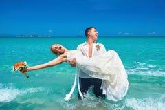 Belle coppie felici sulla spiaggia in vestito da sposa Immagini Stock