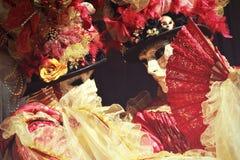 Belle coppie mascherate in colore rosso e ritratto dell'oro Fotografia Stock