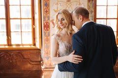 Belle coppie nel supporto del vestito da sposa in museo Guardano l'un l'altro immagine stock