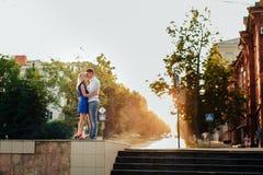 Belle coppie nell'amore con una donna che cammina in un parco su un banco che baciano al tramonto e che si amano, su un vestito b Fotografia Stock Libera da Diritti