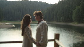 Belle coppie nell'amore in vestiti ucraini tradizionali che abbracciano morbidamente sul pilastro sul lago della montagna breatht video d archivio