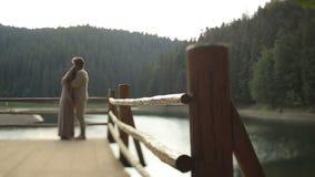 Belle coppie nell'amore in vestiti ucraini tradizionali che abbracciano morbidamente sul pilastro sul lago della montagna breatht stock footage