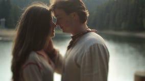 Belle coppie nell'amore in vestiti ucraini tradizionali che abbracciano morbidamente sul pilastro sul lago della montagna Molto o archivi video