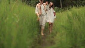 Belle coppie nell'amore in vestiti ucraini tradizionali che camminano a piedi nudi e che si tengono per mano al giacimento verde  video d archivio