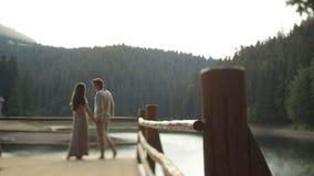 Belle coppie nell'amore in vestiti ucraini tradizionali che si tengono per mano morbidamente sul pilastro sul lago della montagna archivi video