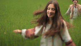 Belle coppie nell'amore in vestiti ucraini tradizionali divertendosi insieme al campo verde stock footage