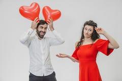 Belle coppie romantiche isolate su fondo bianco Un giovane attraente tiene i palloni sopra la sua testa, la sua fotografie stock