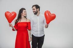 Belle coppie romantiche isolate su fondo bianco Una giovane donna attraente ed il suo marito tengono i palloni e fotografia stock libera da diritti