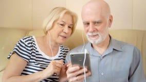 Belle coppie senior allegre che si siedono sul sofà Musica d'ascolto sullo smartphone con le cuffie video d archivio