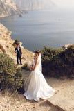 Belle coppie sposa splendida in vestito da sposa che posa con lo sposo elegante su costo del mare Immagini Stock
