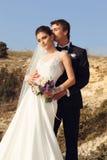 Belle coppie sposa splendida in vestito da sposa che posa con lo sposo elegante su costo del mare Immagine Stock Libera da Diritti