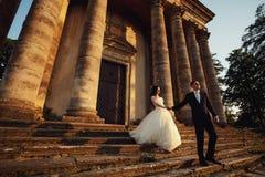 Belle coppie in vestito da sposa all'aperto vicino alla chiesa vittoriana Immagine Stock