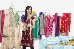 Belle couturière féminine indienne semblant partie tout en travaillant à l'équipement traditionnel Image stock