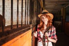 Belle cow-girl heureuse de jeune femme se tenant dans l'écurie Photos stock