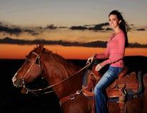 Belle cow-girl sur le cheval dans le coucher du soleil Image stock