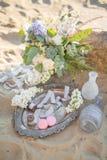Belle décoration élégante avec un bouquet et macarons près de la pierre sur la plage d'une mer Conception l'épousant Images libres de droits