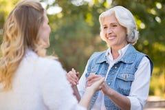 Belle dame âgée de sourire tenant ses mains de filles Images libres de droits