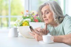 Belle dame âgée lisant un journal Image libre de droits