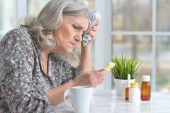 Belle dame âgée prenant des pilules Images stock