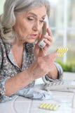 Belle dame âgée prenant des pilules Image stock