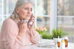 Belle dame âgée prenant des pilules Images libres de droits