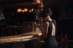 Belle dame élégante avec un smartphone et un verre de vin dans un restaurant Images libres de droits