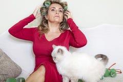 Belle dame avec des bigoudis frottant le chat Photographie stock