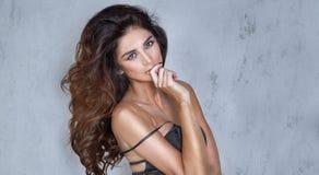Belle dame avec la longue pose bouclée de coiffure Photographie stock libre de droits