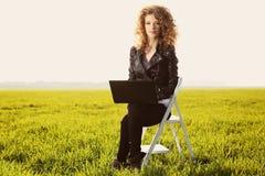 Belle dame avec son ordinateur portable sur l'herbe Photo stock