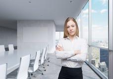 Belle dame d'affaires avec les mains croisées dans le lieu de réunion panoramique avec les fenêtres énormes et la vue de New York image libre de droits