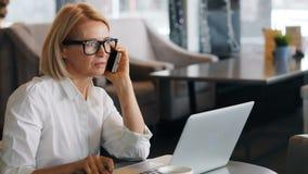 Belle dame d'affaires parlant au téléphone portable vérifiant l'ordinateur portable et le carnet banque de vidéos