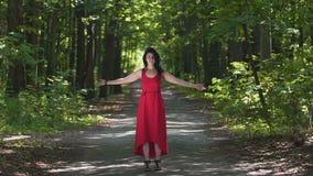 Belle dame dans la robe rouge soulevant les mains dans la forêt, puissance de nature, joie d'unité clips vidéos