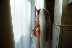 Belle dame sexy de redhair dans la robe de mariage blanche élégante Portrait de mode de modèle à l'intérieur Femme de beauté se t Photographie stock libre de droits