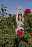 Belle danse asiatique de fille parmi les roses rouges Photo libre de droits