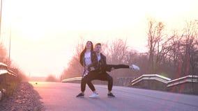 Belle danse de couples sur la route pendant l'aube et sortir l'appui dans le ciel banque de vidéos