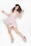 Belle danse de femme de jeune brune dans la robe rose d'isolement au-dessus du fond blanc Images stock