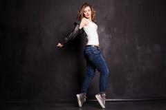Belle danse de fille au mur noir images stock