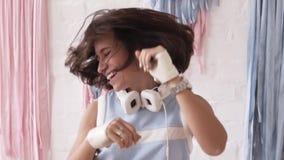 Belle danse heureuse de jeune femme excitée sur le fond rose et bleu Secouant sa tête et dansant en musique banque de vidéos