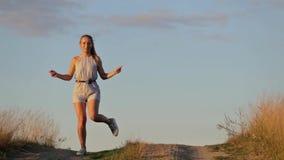 Belle danse heureuse de jeune fille dans un domaine clips vidéos